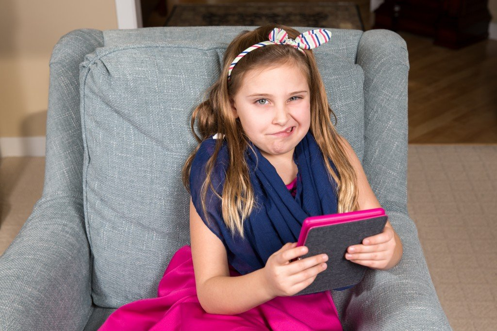 Grimacing Girl in a Chair with a Tablet